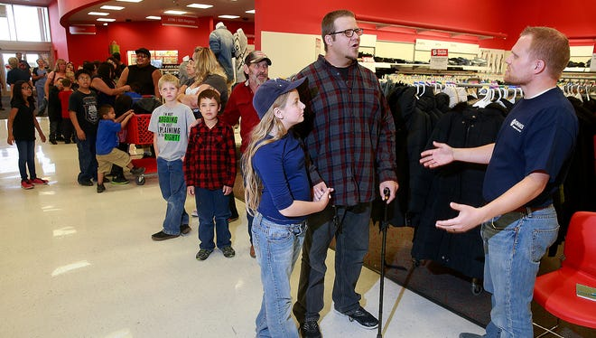 Melodee Edgerton, 10, left, and her dad, Jared Edgerton, center, talk with Brian Turner of the Rio del Sol Kiwanis Club before getting new clothes on Thursday at Target.