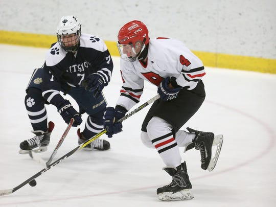 Penfield's Jack Schlifke (4) carries the puck around Pittsford's Bobby Doyle (7).
