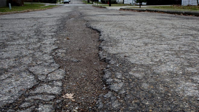 Potholes are seen along Trumbull Street in St. Clair.
