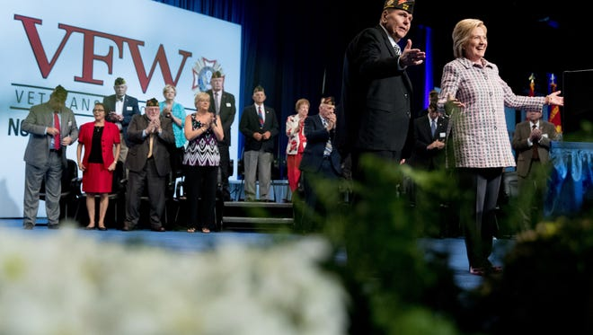 Democratic presidential candidate Hillary Clinton, right, stands on stage with VFW Commander in Chief John Biedrzycki, second from right, after she speaks at the 117th National Convention of Veterans of Foreign Wars at the Charlotte Convention Center in Charlotte, Monday.