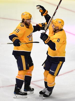 Predators centers Craig Smith (15) and Kyle Turris (8) celebrate the goal by left wing Kevin Fiala (22) during the third period in game 1 of the second round NHL Stanley Cup Playoffs at the Bridgestone Arena Friday, April 27, 2018, in Nashville, Tenn.