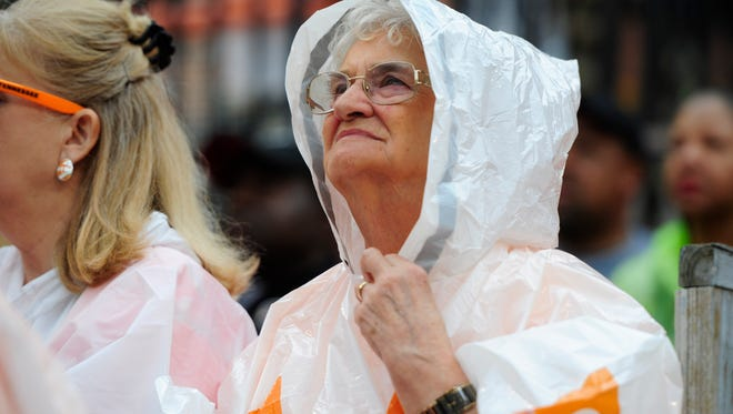 A fan shields herself from the incoming rain during the Orange & White Game at Neyland Stadium in Knoxville, Tennessee on Saturday, April 22, 2017.