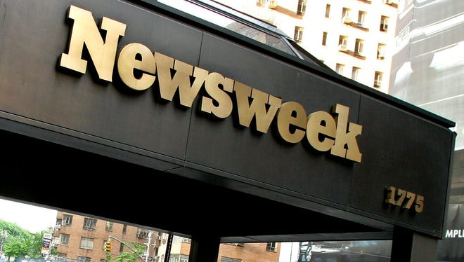 Pedestrians pass by the Newsweek Magazine Headquarters in New York City in May 2005.