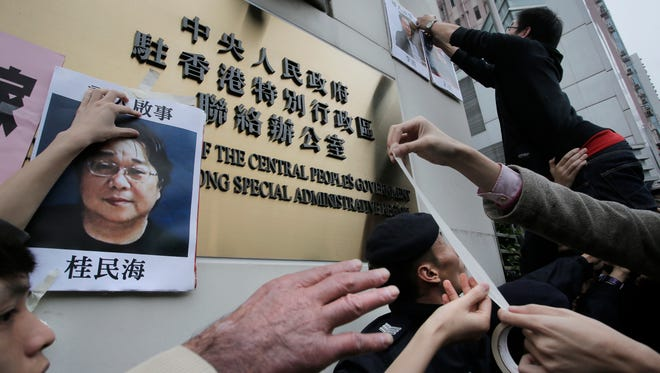Protesters try to stick photos of missing booksellers during a protest outside the Liaison of the Central People's Government in Hong Kong on Sunday. Hong Kong pro-democracy lawmakers say they'll press the government for answers after a fifth employee of a publisher specializing in books critical of China's ruling communists went missing.
