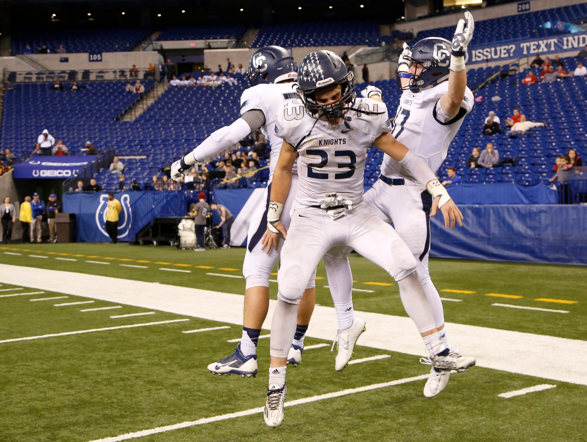 Jacob Page, Jackson Anthrop and Ben Metzinger celebrate afer Central Catholic defeated Linton-Stockton 34-7 in the Class A state finals Friday, November 27, 2015, at Lucas Oil Stadium in Indianapolis.