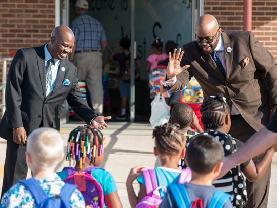 Seaford school board member Jeffrey Benson, left and Pastor Mason McGill welcome students to West Seaford Elementary School.
