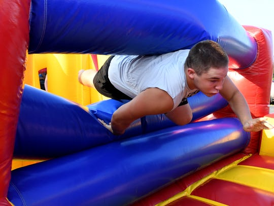 Adamsville's Tristan Coleman goes through an inflatable