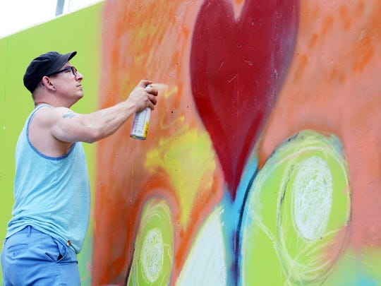 Jimmy Purkey, co-founder of the UpCollective, sprays paint on a Pennsylvania Dutch distelfink at the Penn Street Art Bridge Block Party Saturday, July 29, 2017. The York Time Bank hosted the block party at North Penn and Smyser streets to kick off the Penn Street Art Bridge project. Bill Kalina photo