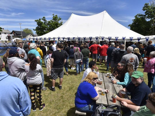 Multiple lines stretch beyond the picnic area waiting for crispy side pork during Side Pork Fest at Martin Park in Sturgeon Bay on Saturday, June 2, 2018. Volunteers grilled 750 pounds of seasoned side pork, which resembles bacon, but not cured or smoked. The festival has increasingly grown in attendance since its inception eight years ago.