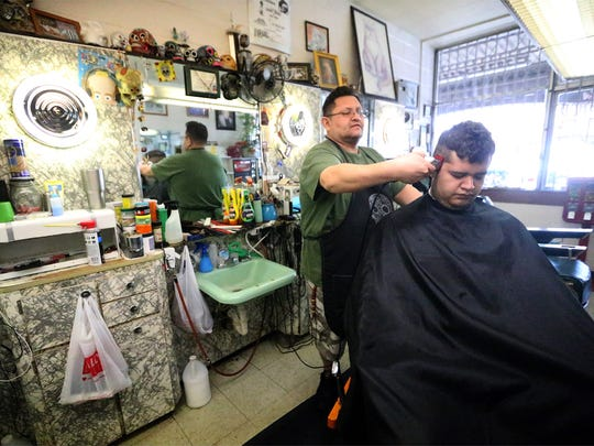 Pablo A. Gonzalez, a barber of 18 years, cuts hair