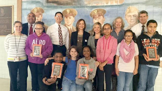 Sixth-grade students at Alexander D. Good Elementary School show off some of their new Kindles, accompanied by teachers Amie Kohler and Jennifer Swartz, Temple Beth Israel Doing Good for Goode project leaders Nada Seidon and Kem Mirsky, TBI Rabbi Jeffrey Astrachan, Principal Randy James and Superintendent Eric Holmes.