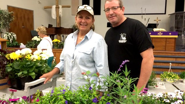 Karen and Jim Thompson load a cart with their selections at the Women of Grace annual plant sale in 2015.