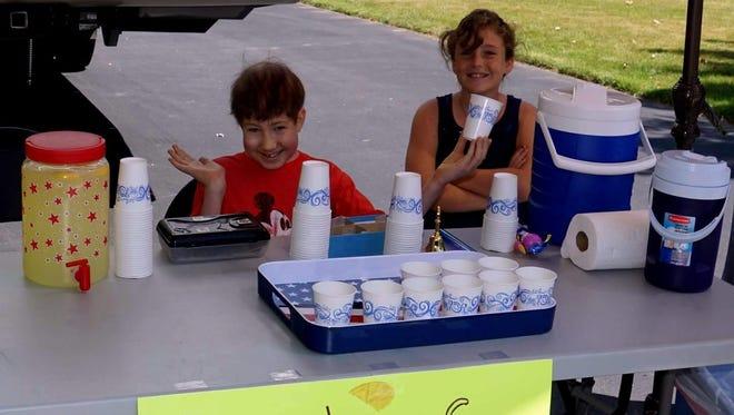 Ben Matthews and his sister Kate serve up lemonade last Saturday at their aunt Linda D'Antonio's home in Webster.