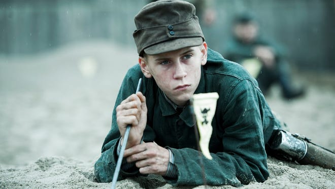 "A Nazi prisoner of war probes the Danish sand for active landmines in ""Land of Mine."""