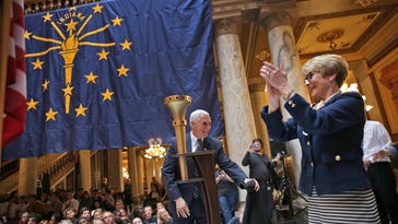 Gov. Mike Pence and Lt. Gov. Sue Ellspermann unveil the Indiana Bicentennial Torch during the Statehood Day Celebration at the Statehouse on Dec. 11.
