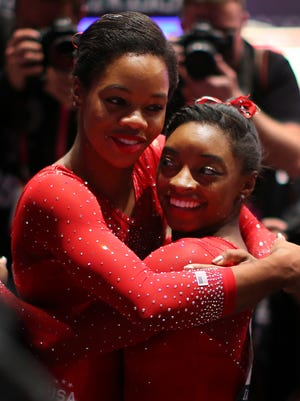 Simone Biles of the U.S. celebrates with team mate Gabby Douglas during day seven of World Artistic Gymnastics Championships at The SSE Hydro on October 29, 2015 in Glasgow, Scotland.