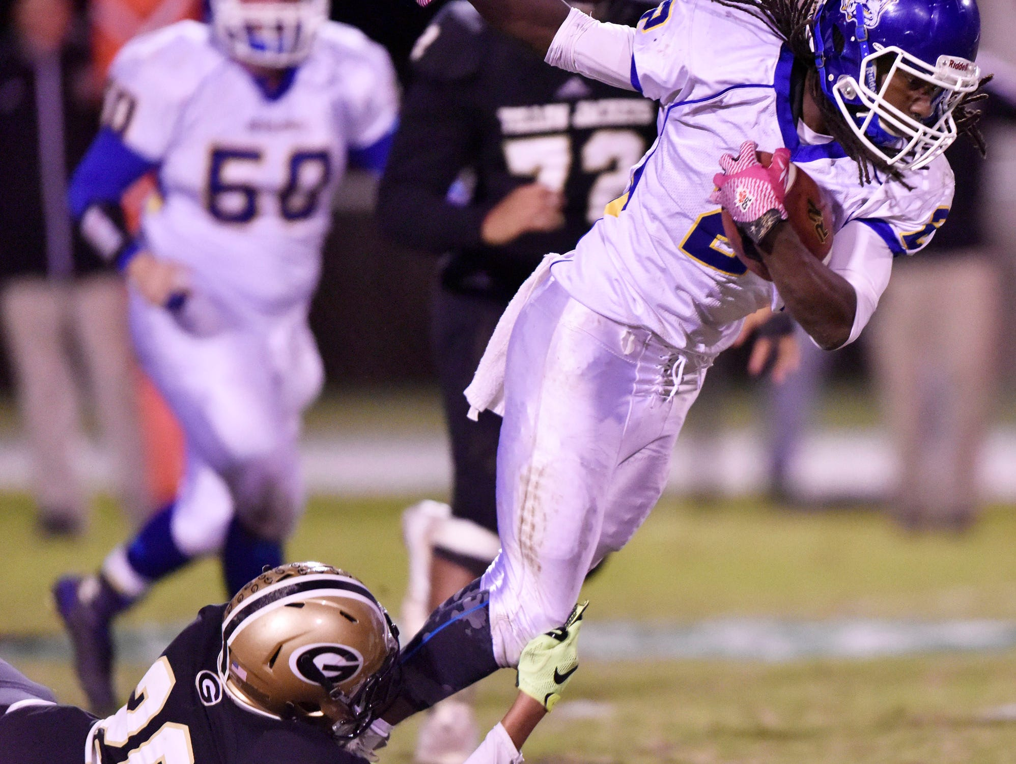 Travelers Rest's Xaiver Terry (2) is caught by Greer's D.J. Sitton (20).