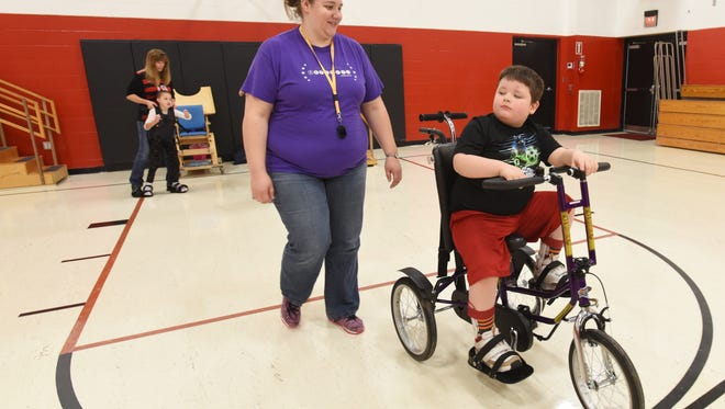 Julieann Spalding follows along as Gabe Conley rides an adaptive bicycle in the gym at Hopewell School in Coshocton. Education at Hopewell is one of the many services and programs offered by the Coshocton County Board of Developmental Disabilities seeking a replacement and addition levy on the November general election ballot.