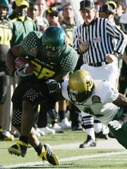 Oregon's Jonathan Stewart, left, was pushed out of