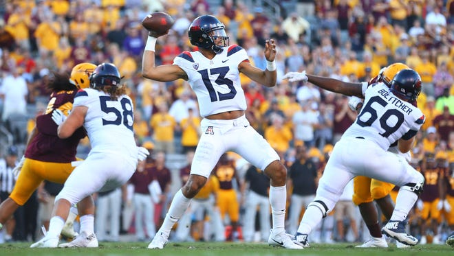 Arizona Wildcats quarterback Brandon Dawkins (13) throws a pass in the third quarter against the Arizona State Sun Devils during the Territorial Cup at Sun Devil Stadium.