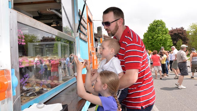 Scott Miller, Myerstown, and his children Cali, 6, and Braylon, 4, make their selections from the Sugar Whipped Bakery Food Truck at the first Food Truck Festival Held at Palmyra on Saturday, May 9, 2015.