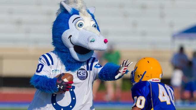 The Indianapolis Colts' mascot, Blue, straight-arms a Carmel player as he rushes the ball out of the backfield. The Indianapolis Colts and the team's mascot, Blue, hosted mascots from around the NFL to as they participated in the third annual Mascot vs. Peewees Football Game at Carmel High School, Thursday, July 12, 2018.