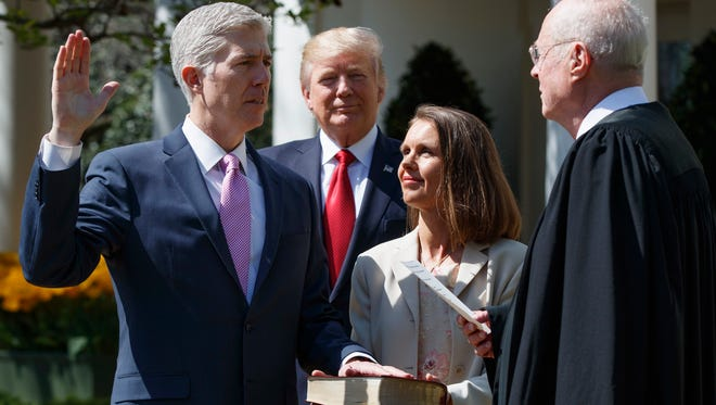 President Donald Trump watches as Supreme Court Justice Anthony Kennedy administers the judicial oath to Justice Neil Gorsuch, accompanied by his wife Marie Louise, during a public swearing-in ceremony in the Rose Garden of the White House in Washington Monday, April 10, 2017. (AP Photo/Evan Vucci)