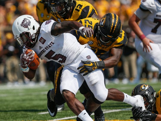 Deion Holliman (5) is brought down by Mizzou defenders