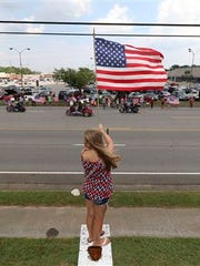 Hailey Lowe, 10, holds a flag high as Patriot Guard