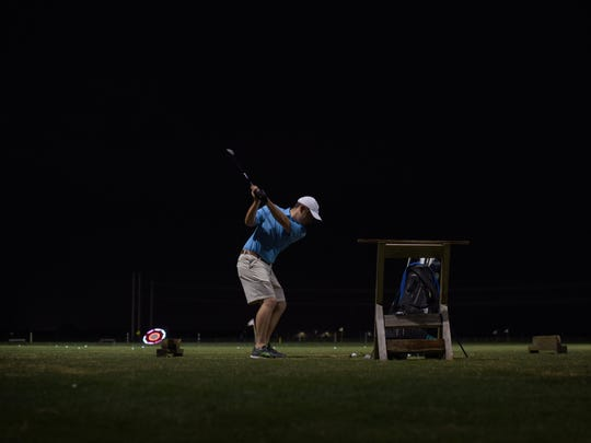 Jordan De Bonis, 22 years old, of Estero, practices his swing at the range at Alico Family Golf in Fort Myers, Sunday evening, December 6, 2015.