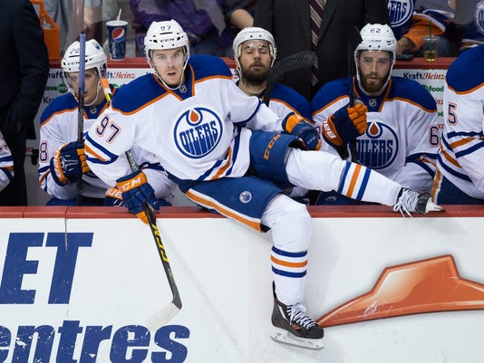 """FILE - In this Oct. 3, 2015, file photo, Edmonton Oilers' Connor McDavid (97) comes off the bench during the second period of a preseason NHL hockey game in Vancouver, British Columbia. Wayne Gretzky was """"The Great One"""" and Mario Lemieux was """"The Magnificent One."""" The hockey world is always looking for a new superstar to transcend the sport. Now, it's McDavid's turn to wear the label and carry the burden that goes with all that hype.  (Darryl Dyck/The Canadian Press via AP, File) MANDATORY CREDIT"""