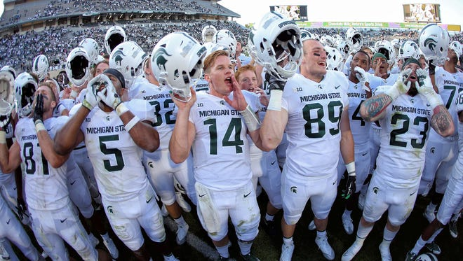 Michigan State Spartans quarterback Brian Lewerke (14) and linebacker Andrew Dowell (5) and tight end Matt Dotson (89) celebrate a win during the second half of a game Sept. 9, 2107, against the Western Michigan Broncos at Spartan Stadium in East Lansing.