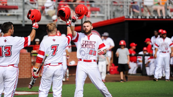 UL's Stefan Trosclair (23) is congratulated after two-run homer in win over ULM that clinched a Sun Belt co-title for the Cajuns.