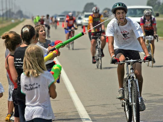 The Boy Scouts of America would frown on children soaking parched RAGBRAI riders with squirt guns as these kids did when the ride came through Waukee in 2006.