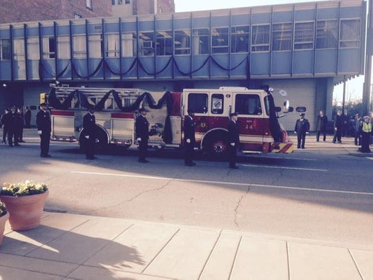 Daryl Gordon's Engine 14 leaves his firehouse at Fifth and Central with pallbearers walking alongside.