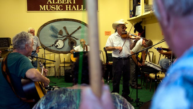 Glenn Borden of  Marlboro plays the fiddle during a jam session in the Pickin' Shed at Albert Hall in Waretown, Ocean County, earlier this month.  Borden began attending jam sessions in the town in the '60s, when he was 19, at a deer hunting cabin  owned by Joe and George Albert. Below: Borden and other musicians play as fans listen on Albert Hall's porch.