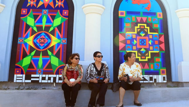 "Linda Miller (from left), Santos Zamora and Tina Salinas sit on the sidewalk after the ribbon cutting for Mayra Zamora's ""Chicano Pop"" mural series on Tuesday, Jan. 24, 2017, at The Art Center of Corpus Christi."