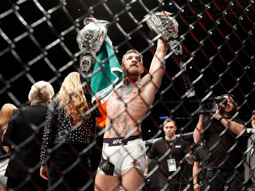 Conor McGregor celebrates with his two championship