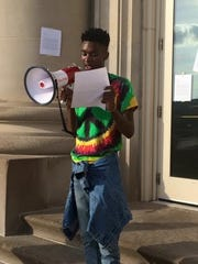 "Avery Jackson, 20, of Des Moines reads a letter at a protest outside of the Des Moines Police Station at 25 E. First St. on Wednesday evening. The letter was addressed to Des Moines Police Chief Dana Wingert. It discussed ""unlawful police profiling and criminalization of Black women, men, and children"" and a ""fatal policing culture."""