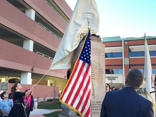 Madeline Thieschafer, daughter of the acting director of St. Cloud VA, unveils the refurbished Abraham Lincoln statue Friday, Nov. 11. The daughter of the first VA director, also named Madeline, unveiled the original statue in 1918.