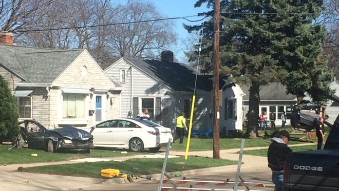 As one side of a car involved in a fatal single-vehicle crash earlier in the day sits in the front yard of a house, on left, the other side is lifted by a tow truck from the lawn of a neighboring house, on right, in the 1100 block of 9th Street in Green Bay on Sunday afternoon, April 16, 2017.
