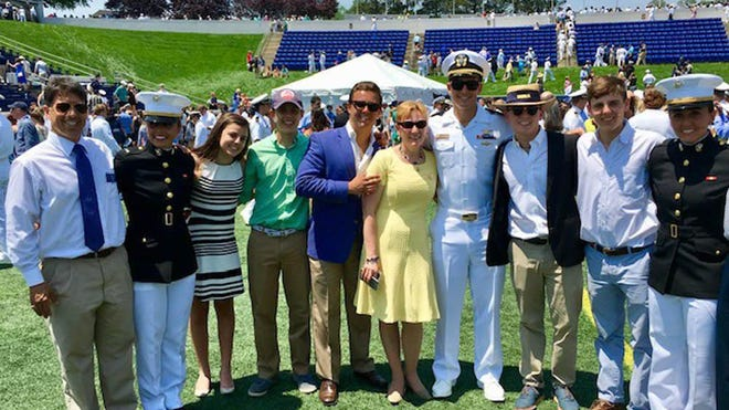 Bud Stark, far left, and Beata Stark, center, yellow dress, pose with their eight children at the 2016 United States Naval Academy graduation in Annapolis, Maryland, where daughters Zofia and Catherine were commissioned to the U.S. Marine Corps. Their children are from left, Zofia, Mary Claire, John Paul, Peter, Joseph, Norman, Francis and Catherine. The Stark family has been selected as the 2020 winner of the Best of Varsity Cup Family Legacy award.