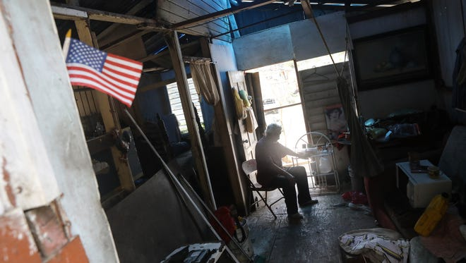 Resident Errol sits in his damaged home without power or running water, decorated with a small American flag, about two weeks after Hurricane Maria swept through the island on Oct 5, 2017 in San Isidro, Puerto Rico. Puerto Rico experienced widespread damage including most of the electrical, gas and water grid as well as agriculture after Hurricane Maria, a category 4 hurricane, swept through.  (