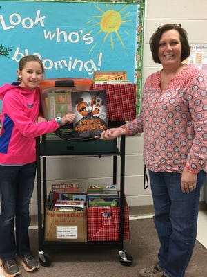 Shown is Sidney Doyle who earned her Girl Scout Bronze Award, the highest award a Junior Girl Scout can receive, presents donated books to Ann Douglas, director of Early Learning for SDOC, at right.