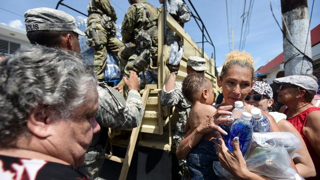 In this Sept. 24, 2017, photo, National Guard Soldiers arrive at Barrio Obrero in Santurce to distribute water and food among those affected by the passage of Hurricane Maria, in San Juan, Puerto Rico.