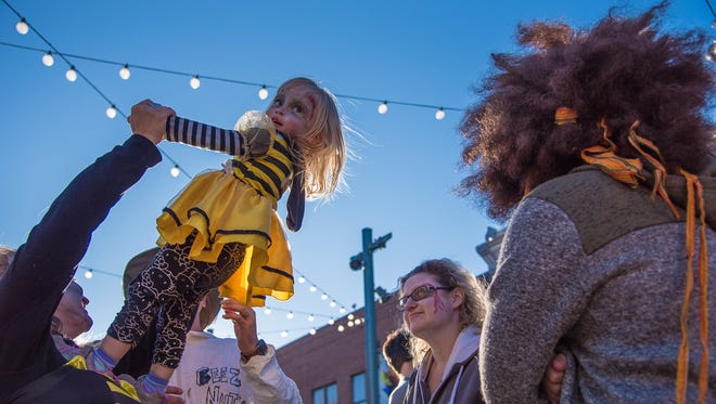 Ariana Scott, 2, is lifted into the air by her mother, Daniela Ripalda, during Zombie Crawl on Saturday, October 21, 2017, in Old Town Square.
