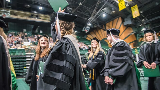 A graduate waves her diploma toward family and friends as she exits a commencement ceremony at Moby Arena on Friday, May 11, 2018. Almost 140 graduates received doctorates from the College of Veterinary Medicine and Biomedical Sciences.