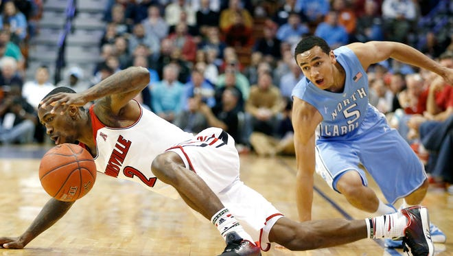 Louisville's Russ Smith (2) goes out of bounds after losing control of the ball against North Carolina's Marcus Paige (5) during the second half of an NCAA college basketball game in the Basketball Hall of Fame Tip-Off tournament championship at Mohegan Sun Arena in Uncasville, Conn.