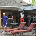 Northwestern State guard Jalan West takes a shot while university president Jim Henderson walks past.
