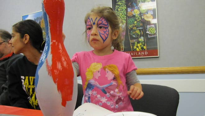 """""""Champion Children"""" at Children's Hospital Medical Center are painting the trophies for the """"Let the Good Times Bowl"""" fundraiser."""